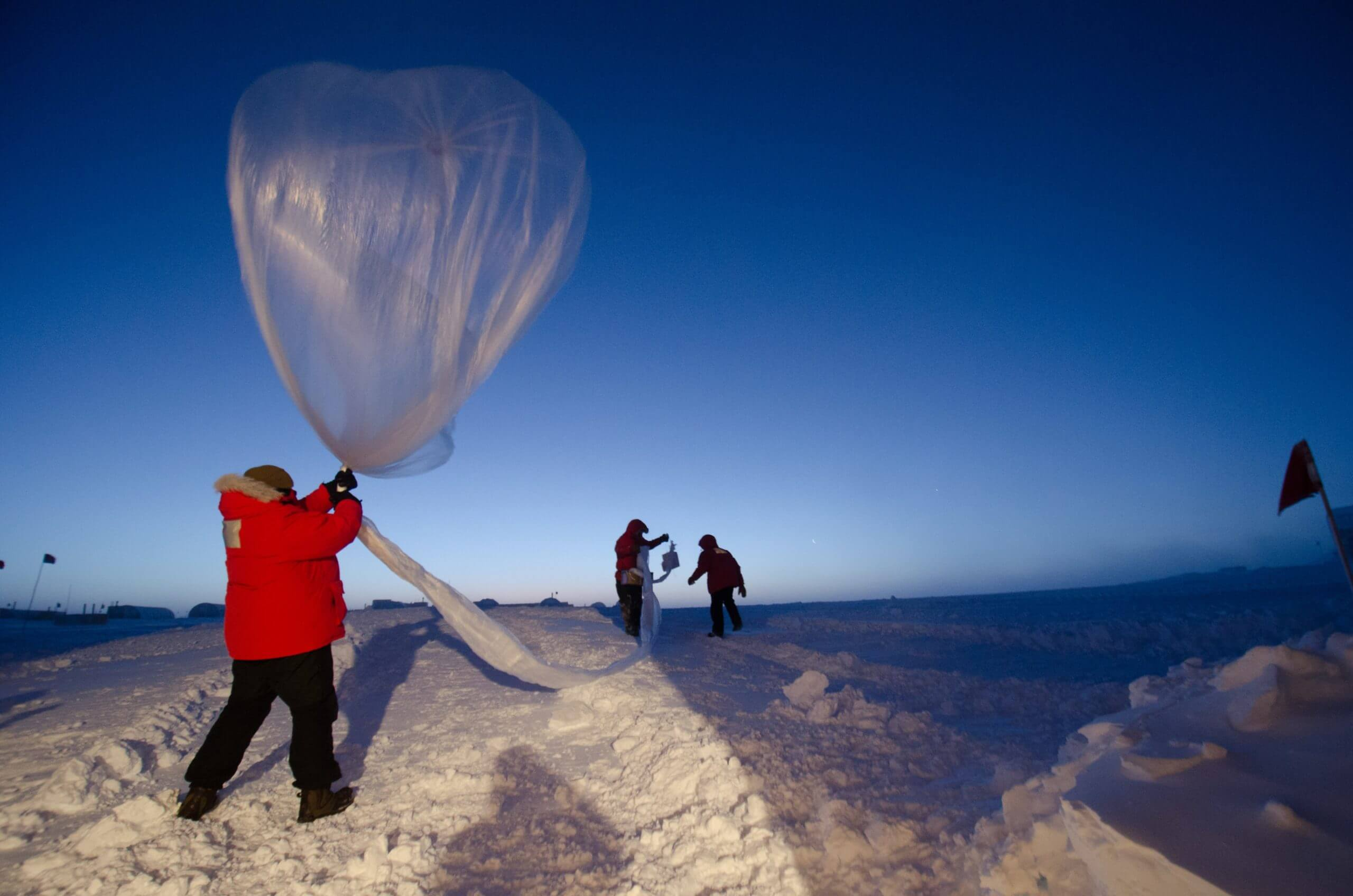 a group of people conducting an experiment where one is trying to fly a balloon